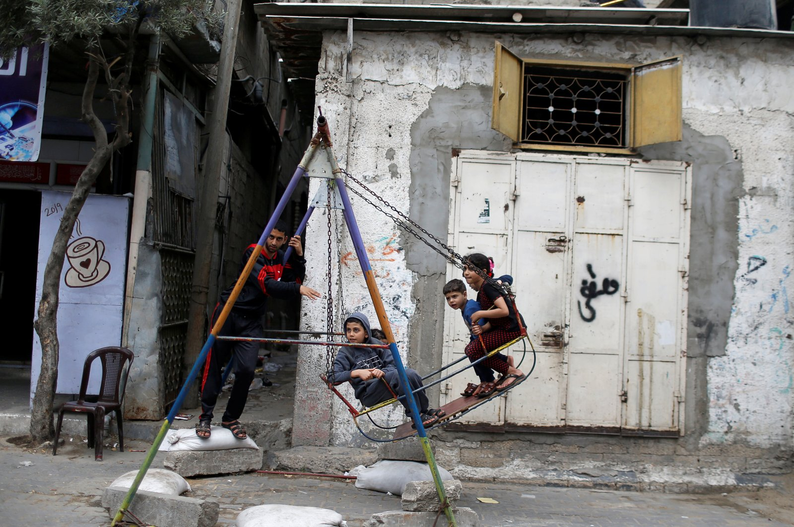 Palestinian children play on a swing in Jabalia refugee camp, Gaza, Palestine, May 5, 2020. (Reuters Photo)