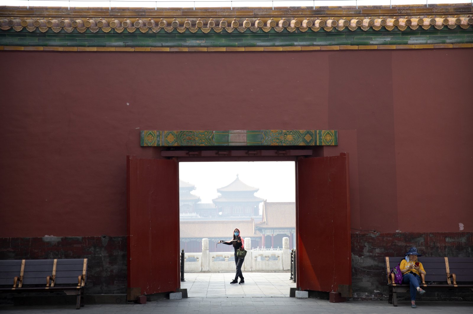 A visitor wearing a face mask to protect against the coronavirus walks through the Forbidden City in Beijing, May 1, 2020. (AP Photo)