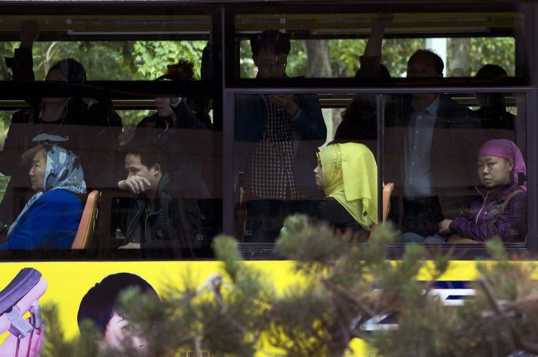 Ethnic Chinese and Uighur commuters take a public bus in Urumqi, China's northwestern region of Xinjiang, May 23, 2014. (AP Photo)