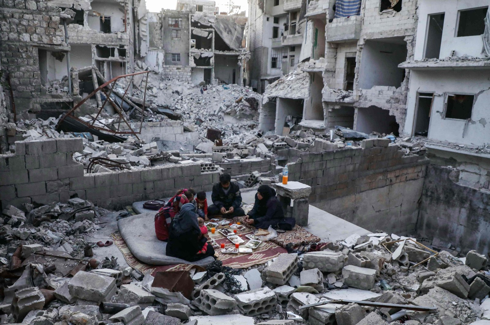 """Members of the displaced Syrian family of Tariq Abu Ziad, from the town of Ariha in the southern countryside of Idlib province, break their fast together for the sunset """"iftar"""" meal in the midst of the rubble of their destroyed home upon their return to the town, May 4, 2020. (AFP)"""