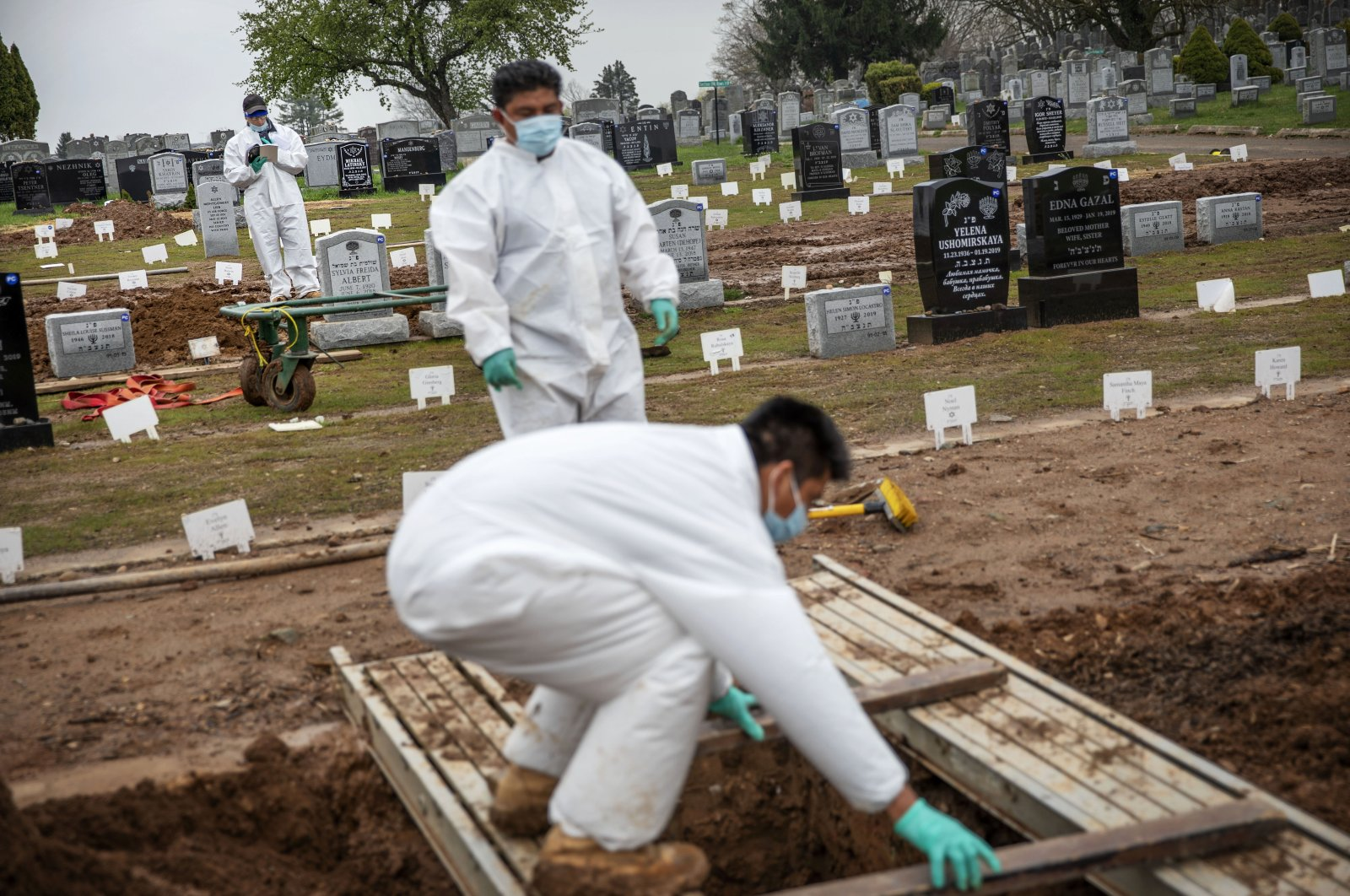 A rabbi (in the background) finishes a prayer during a burial service as gravediggers prepare a plot for the next burial at a cemetery in Staten Island, New York, April 8, 2020. (AP Photo)