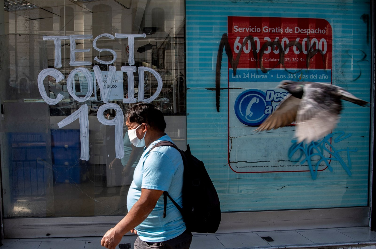 A person walks past a pharmacy where COVID-19 tests are conducted in Recoleta commune, which was placed under quarantine last night to slow the spread of the novel coronavirus COVID-19, in Santiago, Chile on May 06, 2020. (AFP Photo)