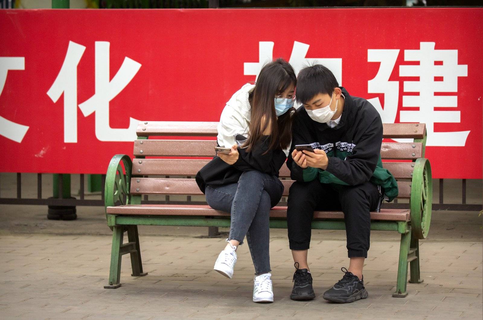 People wearing face masks to protect against the spread of the new coronavirus sit on a bench in front of a propaganda banner encouraging people to wear masks at a public park in Beijing, Thursday, May 7, 2020. (AP Photo)