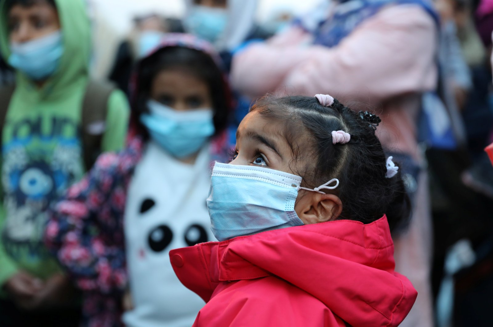 A migrant girl from the Moria camp in Lesbos waits to board a bus at Piraeus port in Athens following the coronavirus disease (COVID-19) outbreak, Greece, May 4, 2020. (Reuters Photo)