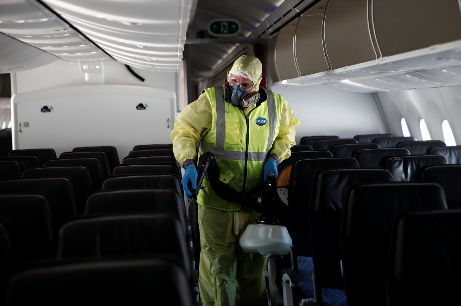 A worker, wearing a protective suit, sprays disinfectant inside an Air France Boeing 787 aircraft during a presentation of new security and health measures at Paris Charles de Gaulle airport in Roissy-en-France during the outbreak of the coronavirus in France, May 6, 2020. (Reuters Photo)