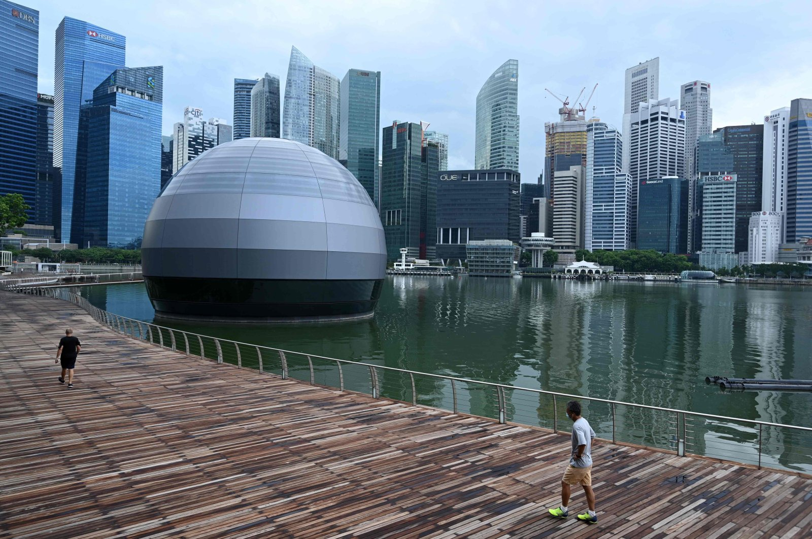 People wearing face masks as a preventive measure against the spread of the COVID-19 outbreak walk along the promenade at Marina Bay in Singapore, May 4, 2020. (AFP Photo)