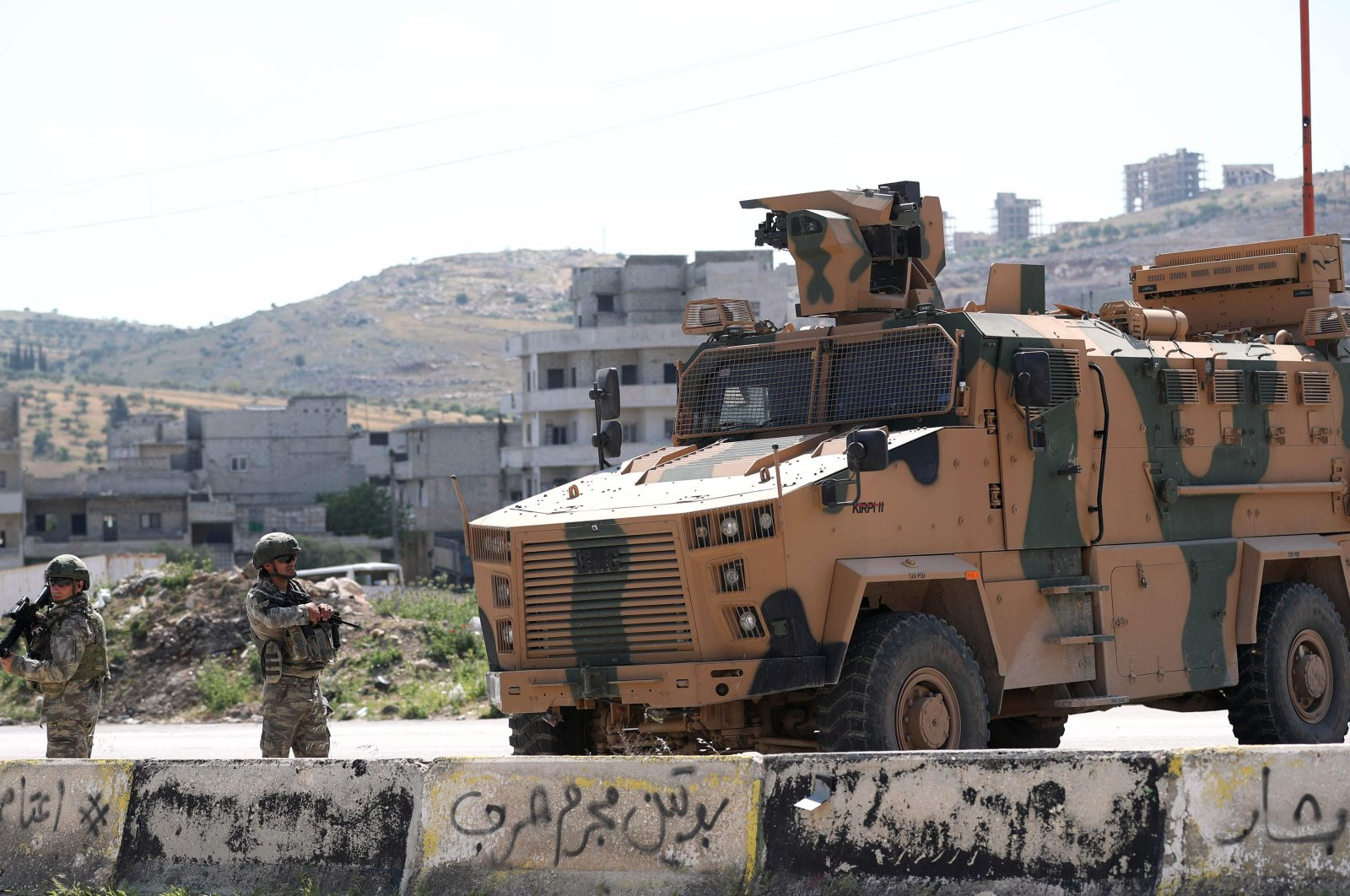 Turkish troops stand next to one of their armoured vehicles as they secure the road on the M4 highway between Saraqeb and Ariha in Syria's Idlib province, May 7, 2020. (AFP)
