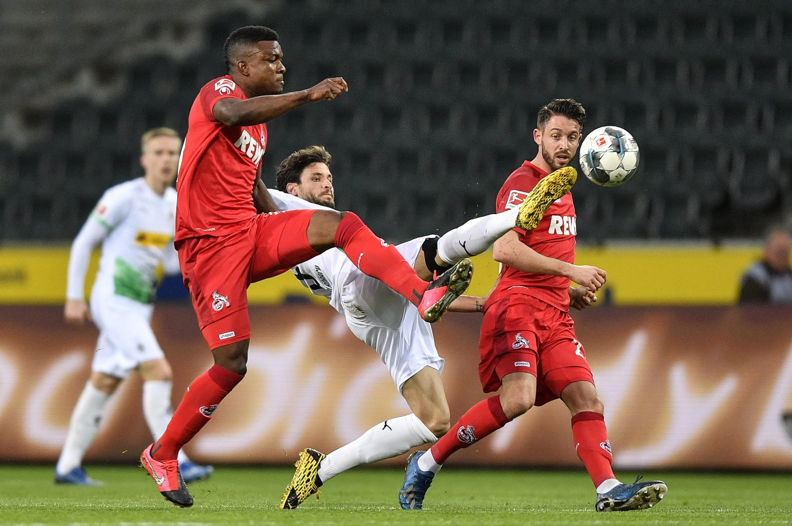 Cologne's Jhon Cordoba and Moenchengladbach's Tobias Strobl challenge for the ball during a Bundesliga match in Moenchengladbach, Germany, March 11, 2020. (AP Photo)