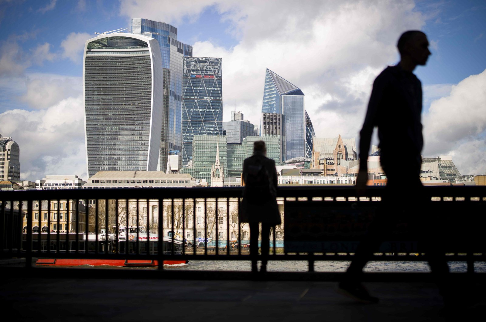 Pedestrians walk by with the towers of the City of London in the background in London, March 11, 2020. (AFP Photo)