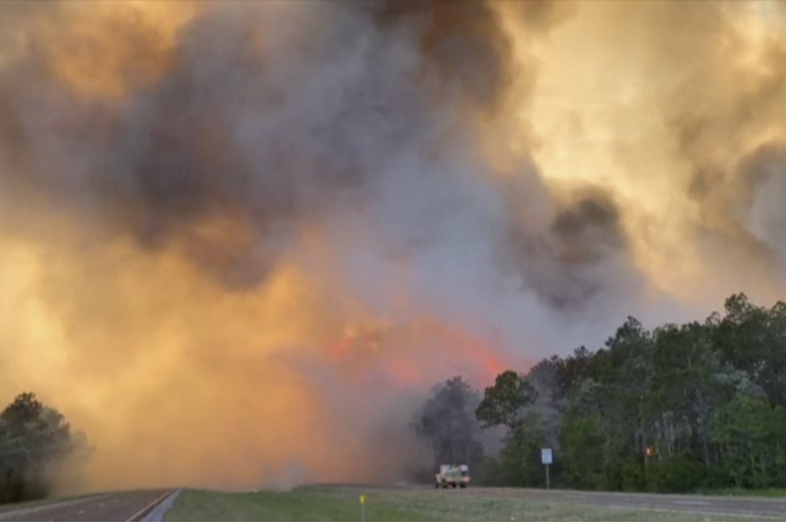 In this image made from video taken May 6, 2020 by the Florida Department of Agriculture and Consumer Services, fire and smoke rise from trees alongside a road in Santa Rosa County, Florida. (AP Photo)