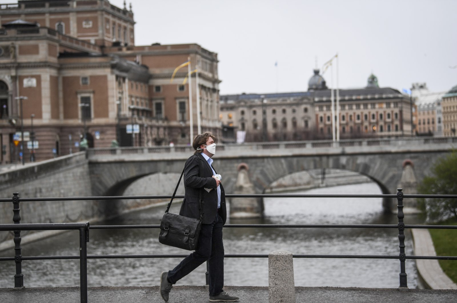 A man wearing a protective mask walks in the rain past the Royal Swedish Opera (at left) in Stockholm, Sweden, 27 April 2020, amid the coronavirus disease (COVID-19) outbreak.  (EPA-EFE Photo)