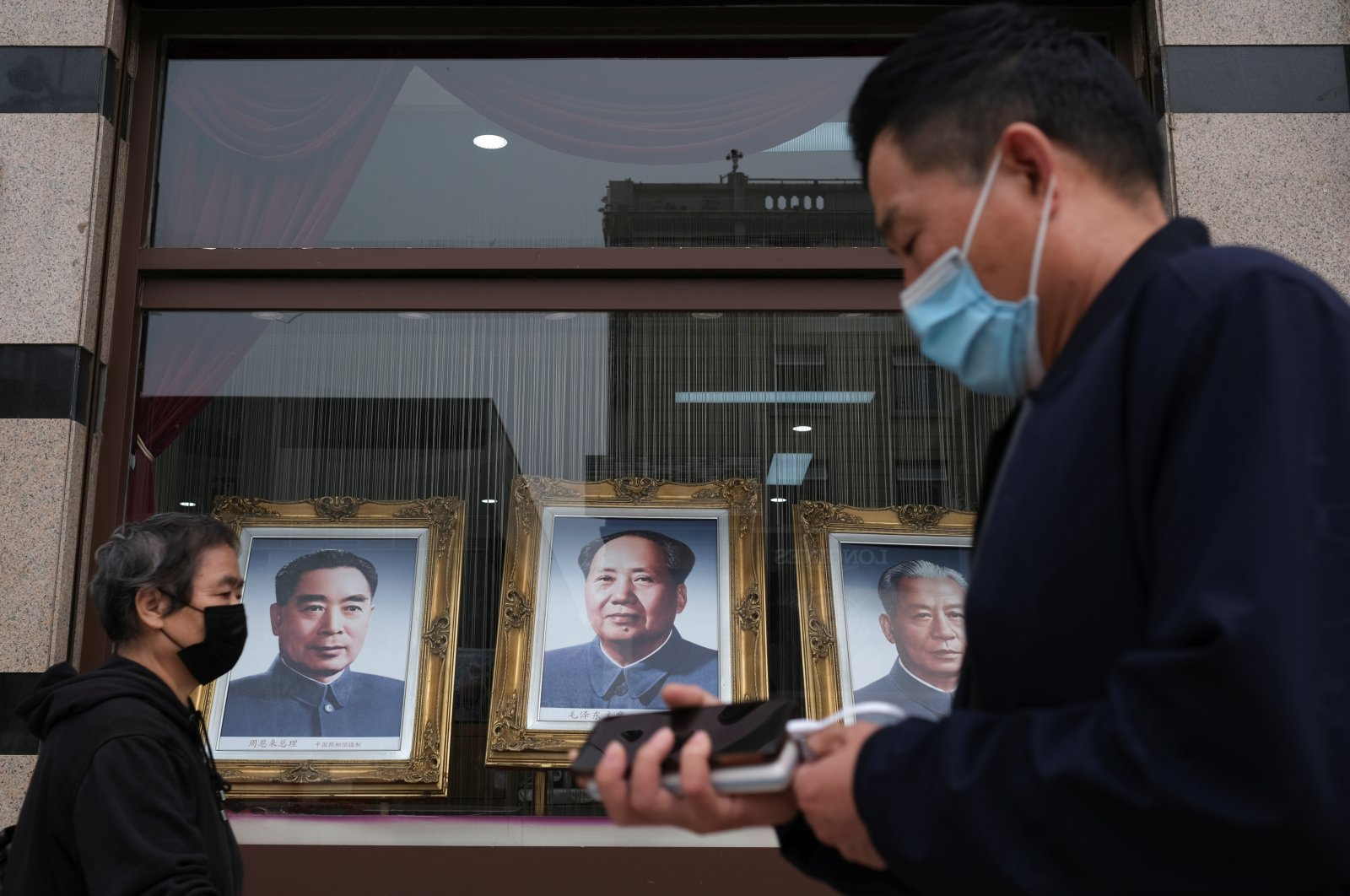 People wearing face masks walk past portraits of late Chinese Communist Party leaders (L-R) Zhou Enlai, Mao Zedong and Liu Shaoqi at Wangfujing street, following an outbreak of the coronavirus disease (COVID-19), in Beijing, China, May 7, 2020. (Reuters Photo)
