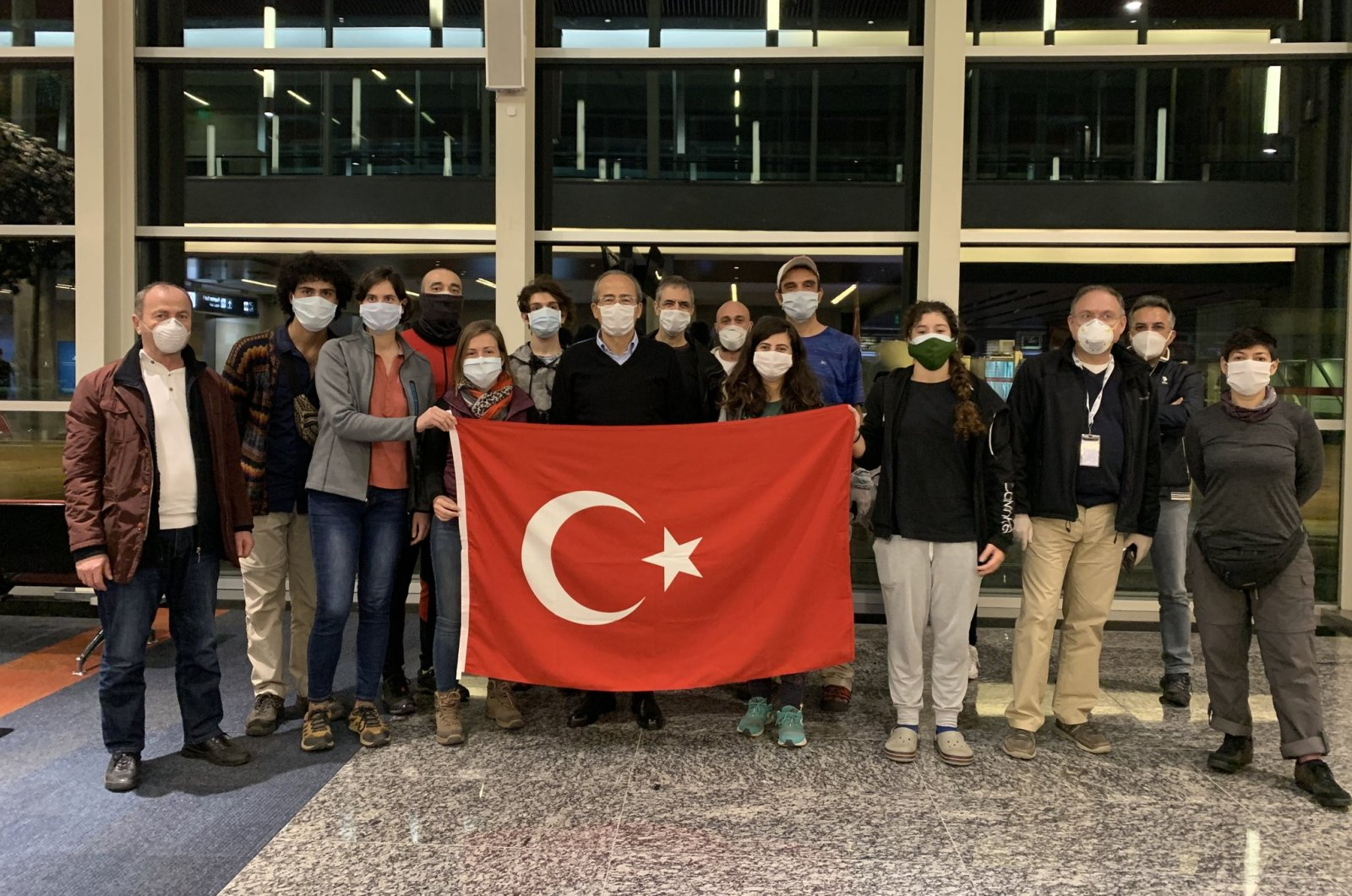 Evacuated Turkish nationals pose with a Turkish flag at an airport in Buenos Aires, Argentina, May 6, 2020. (AA Photo)