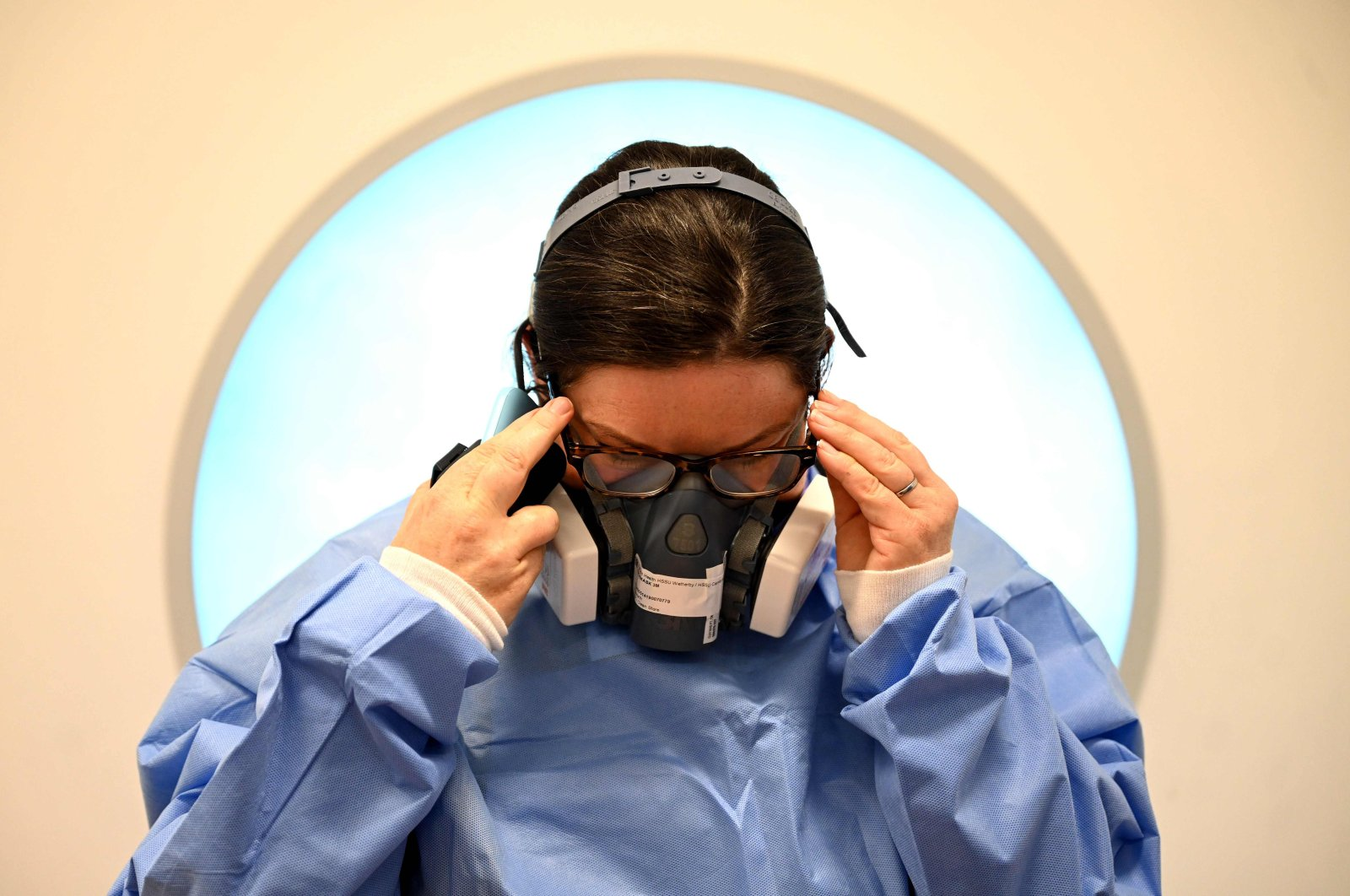 A member of the clinical staff adjusts her glasses as she dons personal protective equipment (PPE) including a mask and gown at the Intensive Care unit at Royal Papworth Hospital in Cambridge, on May 5, 2020. (AFP File Photo)