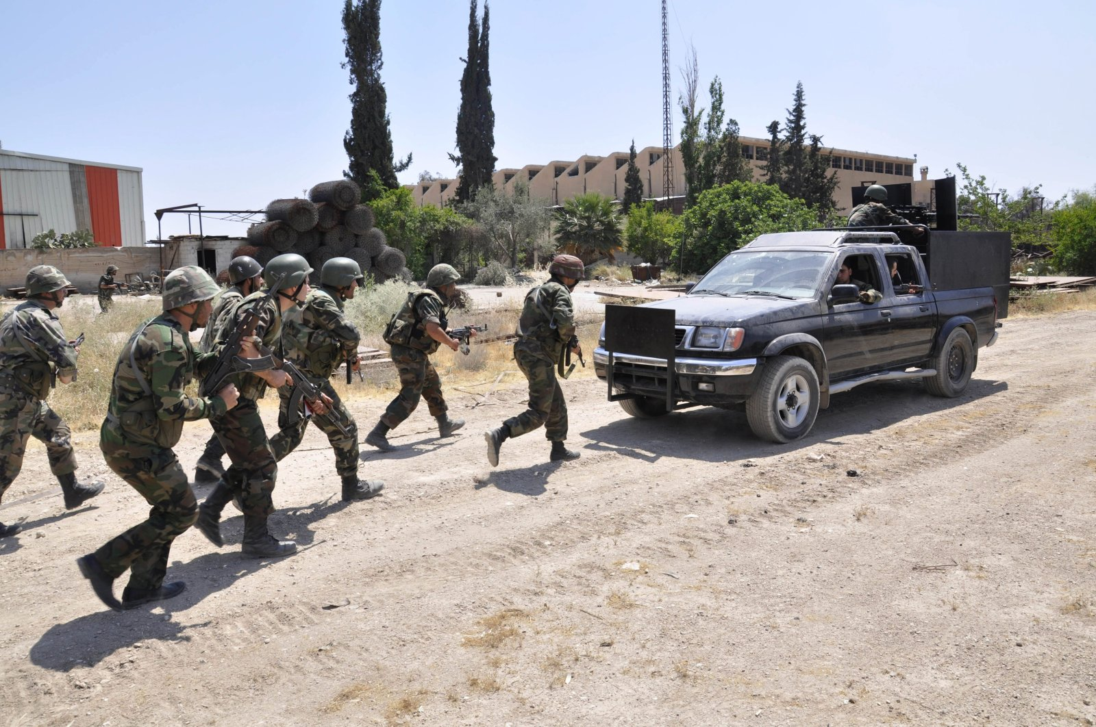 In this file photo released on Sunday, May 26, 2013, by the Syrian official news agency SANA, Syrian forces loyal to Bashar Assad take their position during clashes in Aleppo, Syria. (AP Photo)