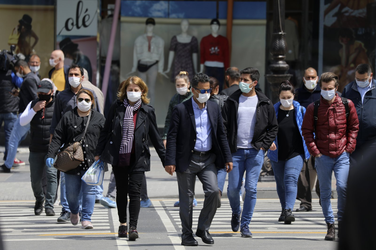 People wearing face masks for protection against the coronavirus, walk in a busy street, in Ankara, Turkey, Tuesday, May 5, 2020. (AP Photo)