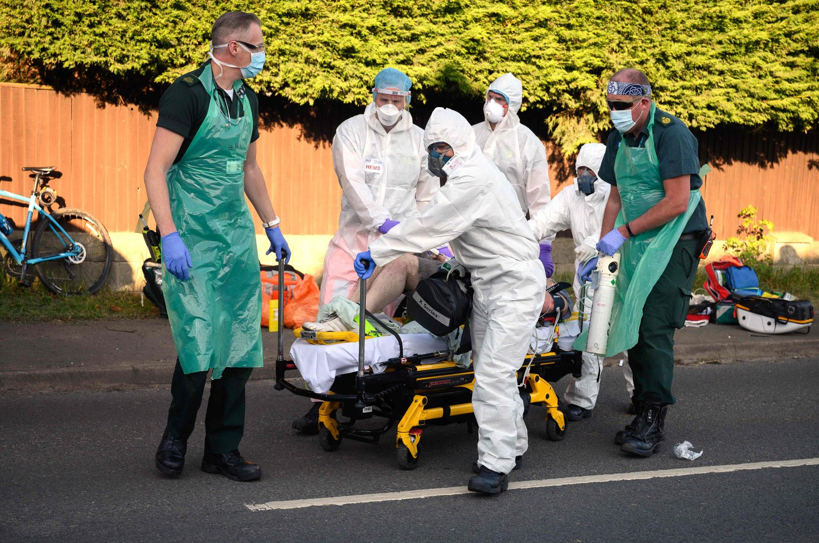 Ambulance and air ambulance crews wearing personal protective equipment (PPE) work to stabilize a patient with possible COVID-19 symptoms who was found unconscious having suffered a cardiac arrest while cycling in Botley, near Southampton, southern England, May 6, 2020. (AFP Photo)
