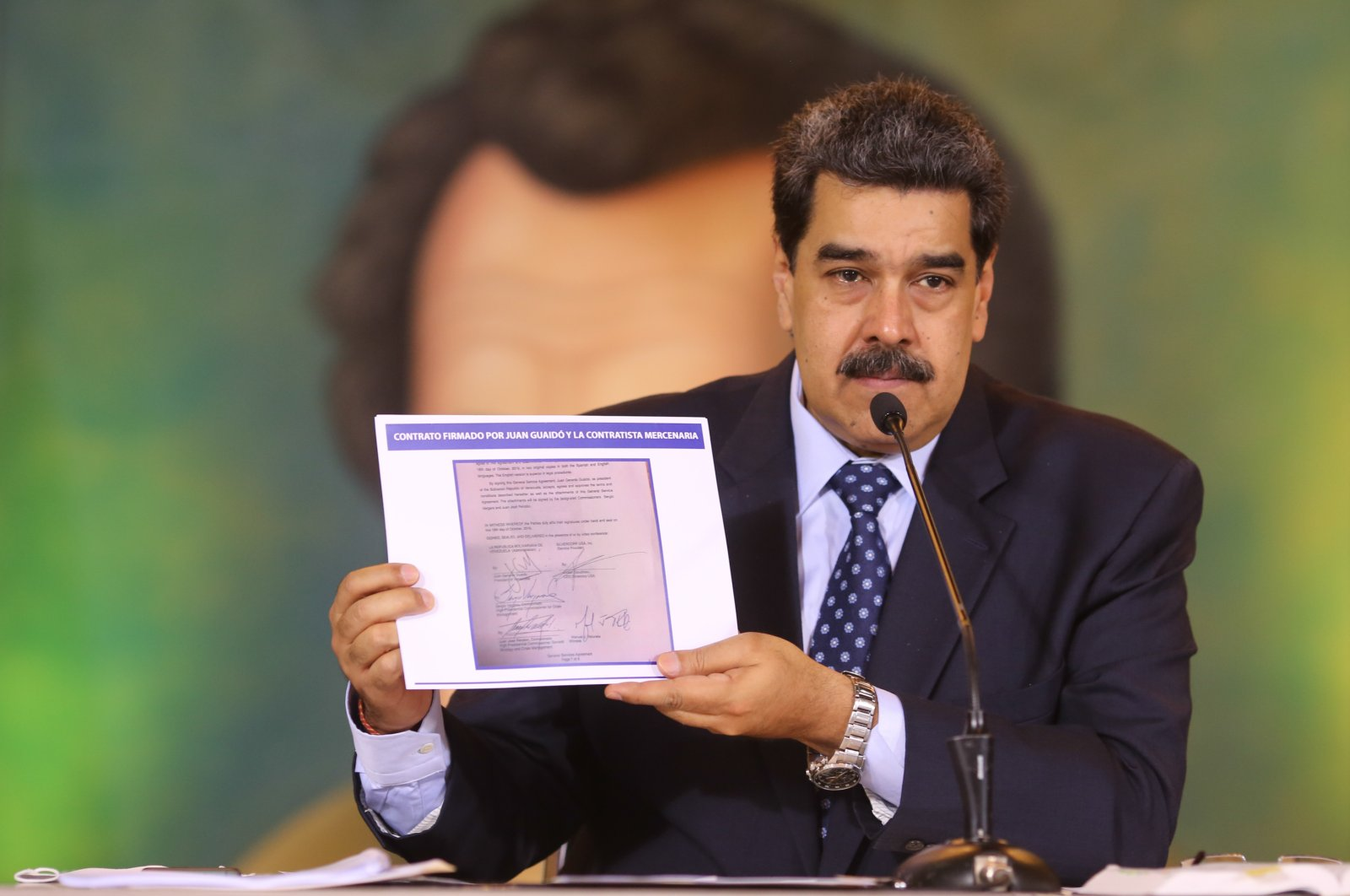 President Nicolas Maduro holds a copy of a written agreement that allegedly bears Guaido's signature as evidence during an online press conference, Caracas, May 6, 2020. (AP Photo)
