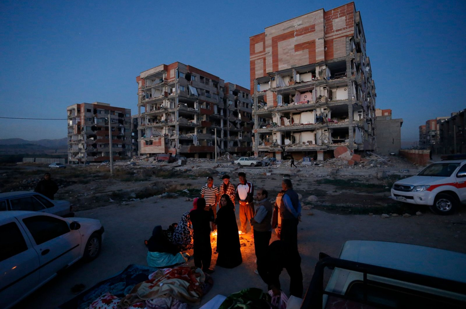 Residents huddle by a fire in an open area following a 7.3-magnitude earthquake at Sarpol-e Zahab in Iran's Kermanshah province, Nov. 13, 2017. (AFP Photo)