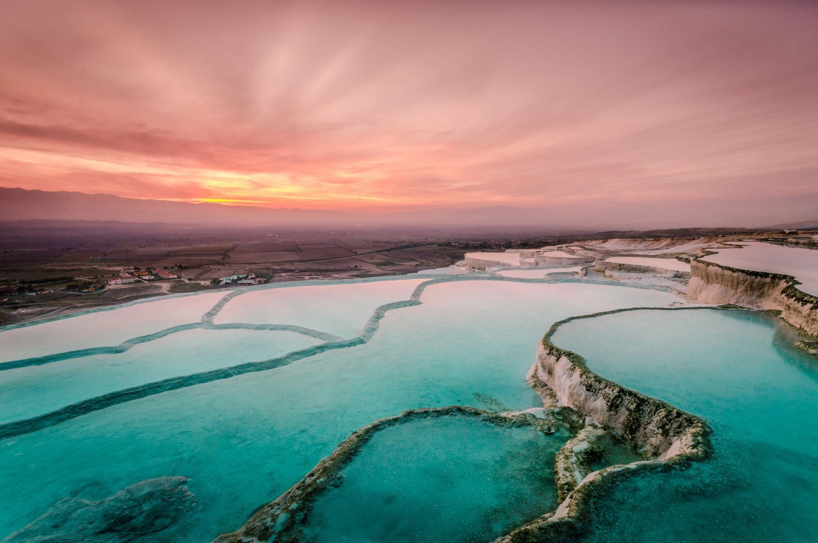 The natural pools created by the carbonate travertines are spectacular during sunset. (iStock Photo)