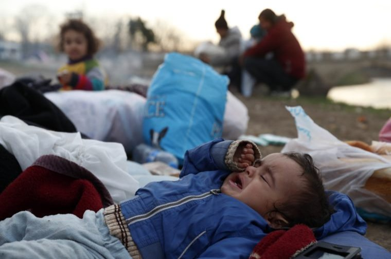 A baby cries as migrants gather next to a river in Edirne, Turkey, near the Turkish-Greek border, March 4, 2020. (AP Photo)