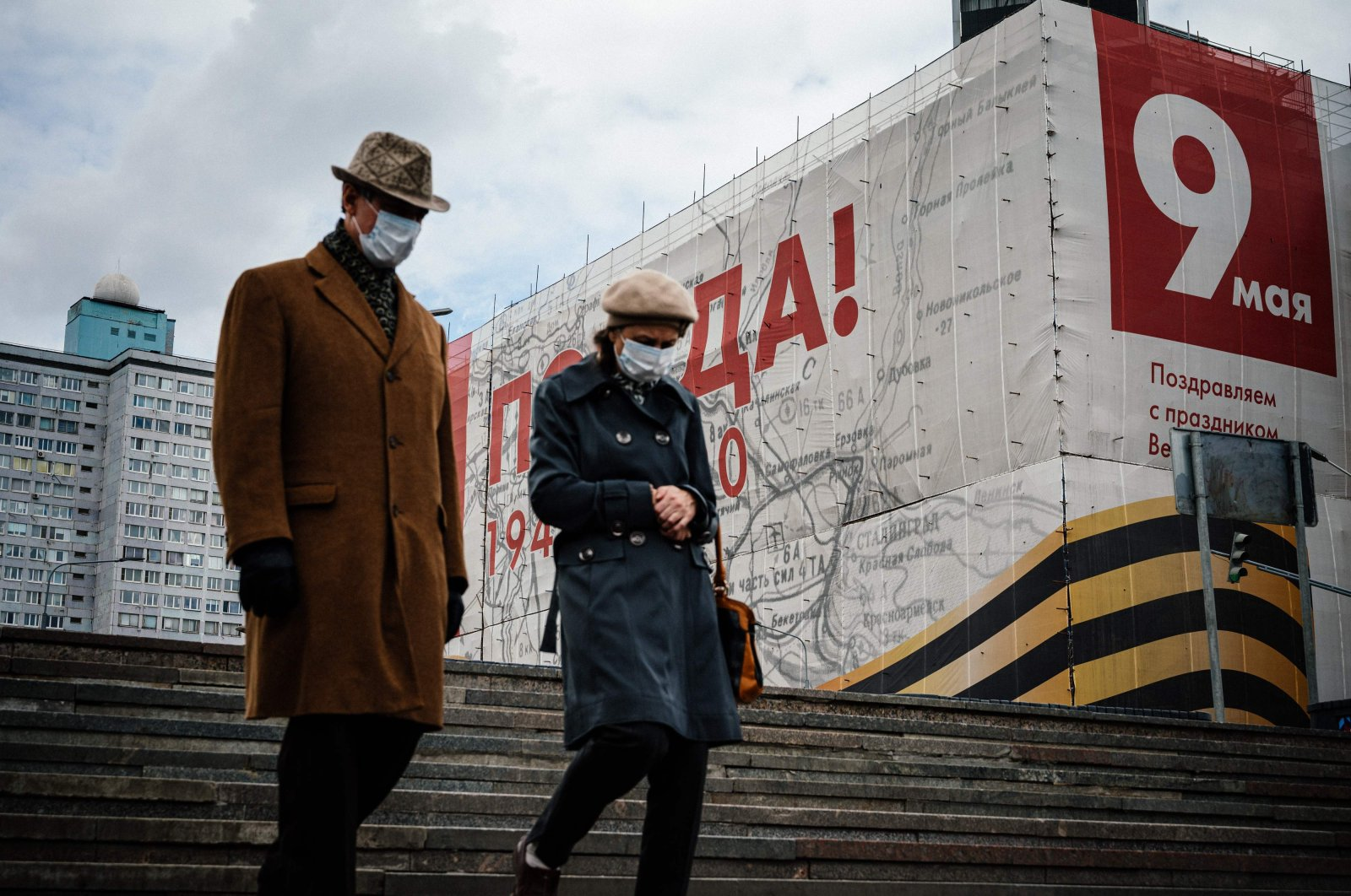 A couple wearing face masks walks in front of a huge banner for the upcoming 75th anniversary of the Soviet victory over Nazi Germany in World War II that is used to cover a building under renovation, Moscow, Russia, May 7, 2020. (AFP Photo)