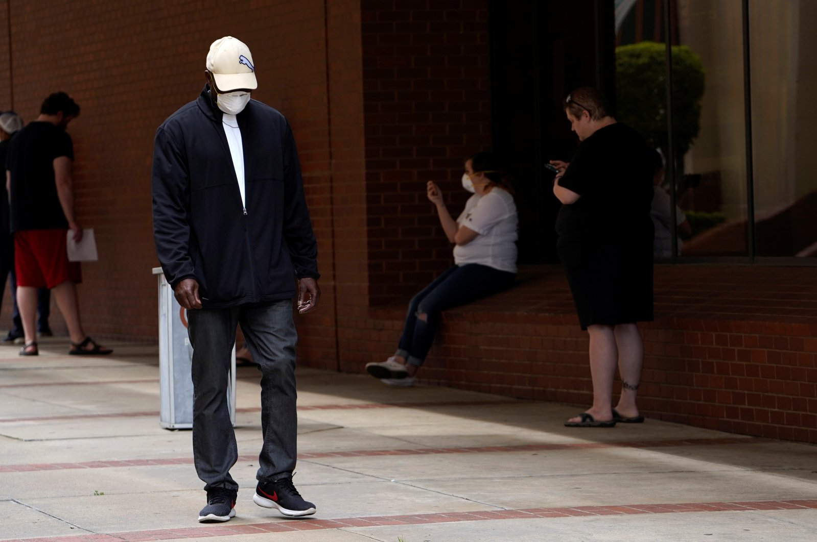 A man who lost his job walks past others as they wait in line to file for unemployment during the coronavirus pandemic, at an Arkansas Workforce Center in Fort Smith, Arkansas, U.S., April 6, 2020. (Reuters Photo)
