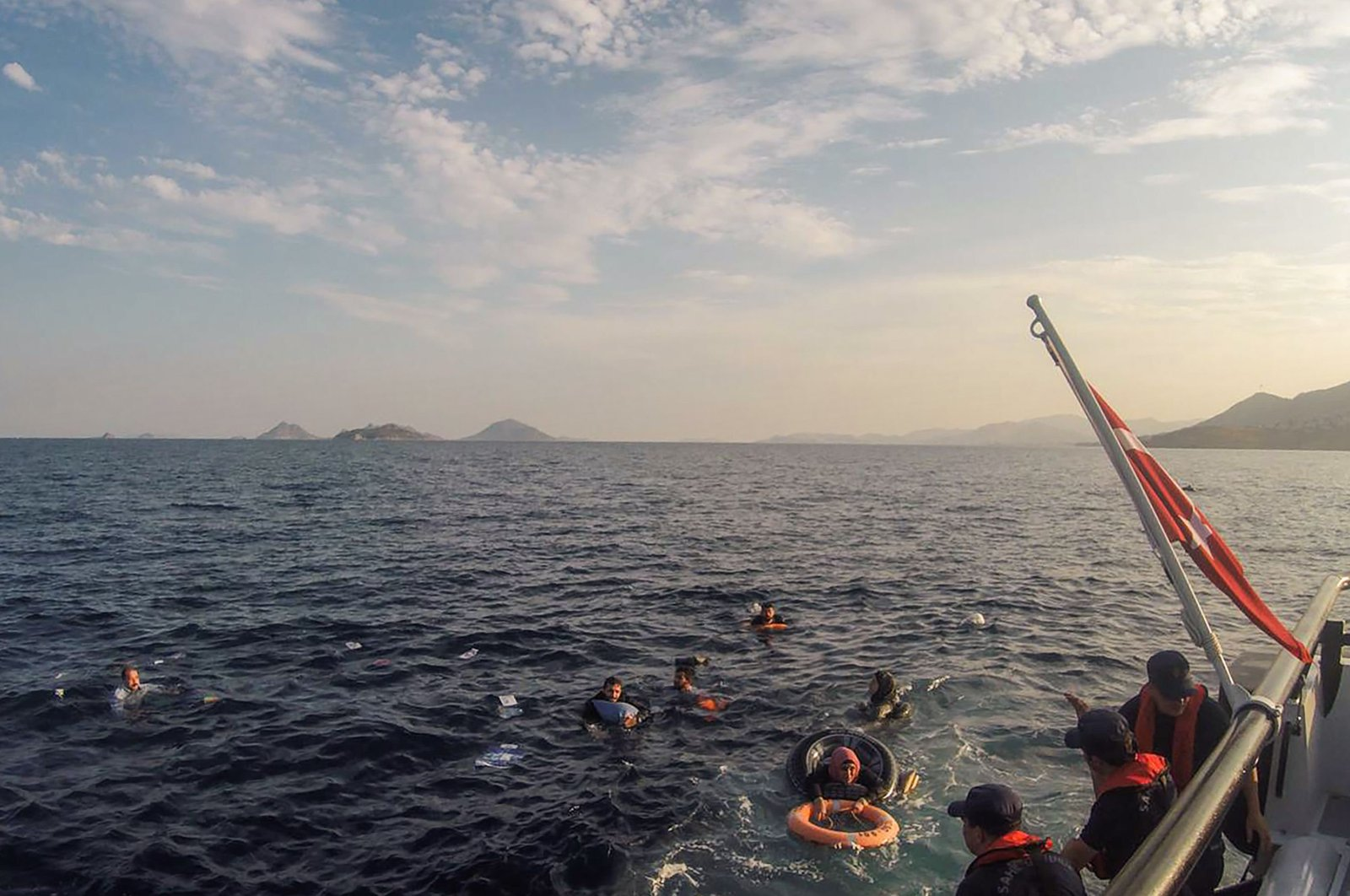 This handout picture released and taken on June 17, 2019, by the Turkish coastguard shows illegal migrants being rescued after their boat sank in the Aegean sea, off the coast of southwestern Turkey. (AFP File Photo)