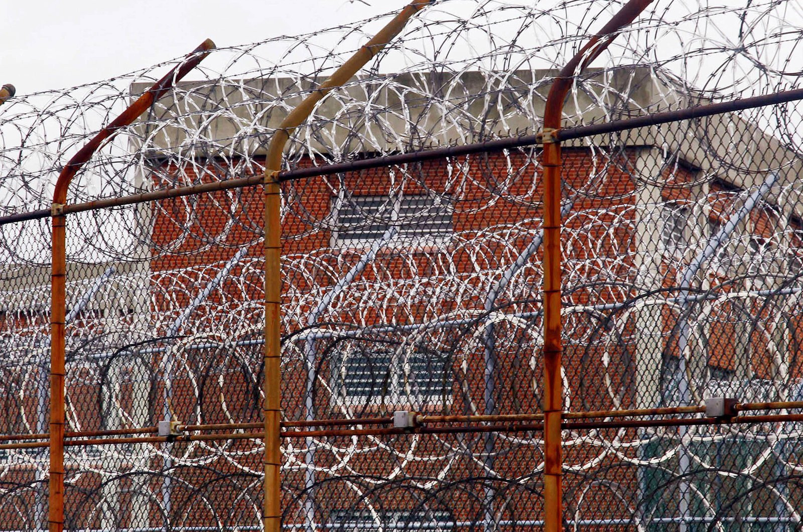 In this March 16, 2011, file photo, a security fence surrounds inmate housing at the Rikers Island correctional facility in New York. As of May 6, 2020, more than 20,000 inmates have been infected by the coronavirus and 295 have died nationwide, according to an unofficial tally kept by UCLA Law's COVID-19 Behind Bars Data Project. (AP File Photo)