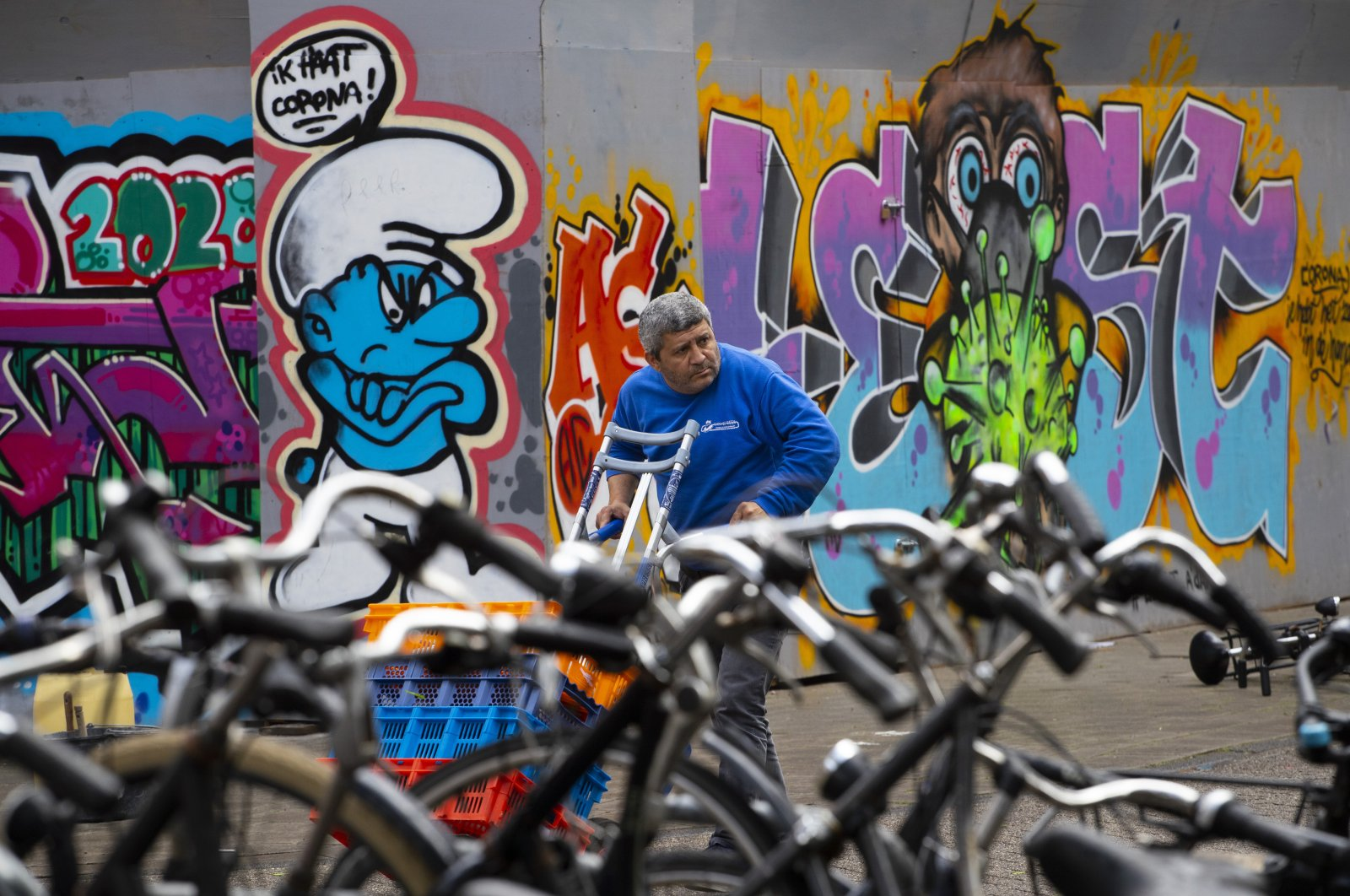 """A man delivering goods passes two COVID-19 related murals, one of a smurf reading """"I Hate Corona,"""" Amsterdam, the Netherlands, May 1, 2020. (AP Photo)"""