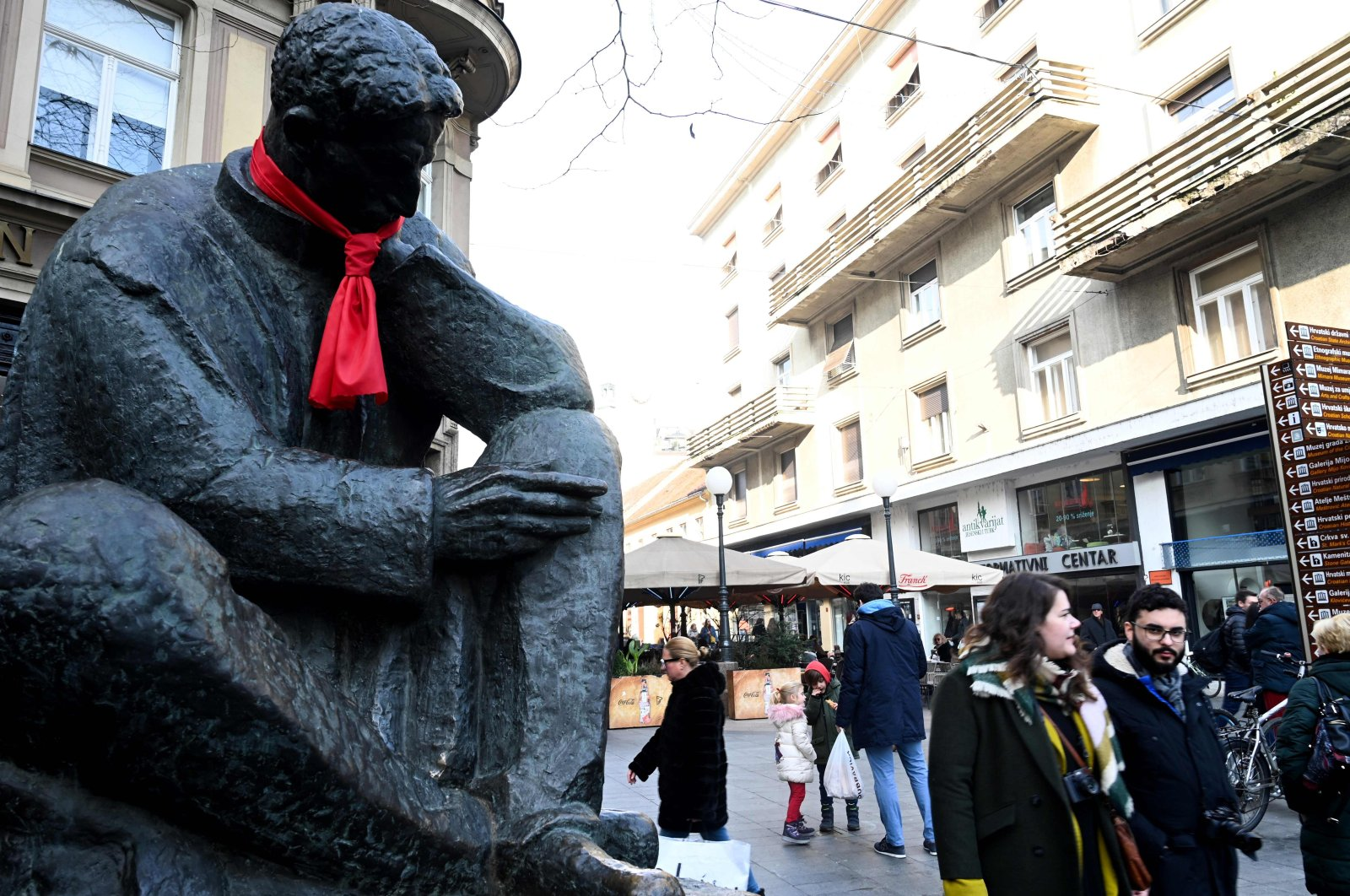 People walk past a statue of Nikola Tesla, one of the pioneers of modern electrical engineering, with a red tie knotted around the neck symbolizing Croatia's taking over the EU's rotating presidency of the EU Council, in central Zagreb, Jan. 3, 2020. (AFP Photo)