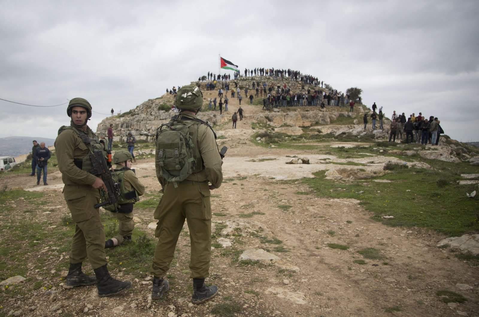 Israeli soldiers take position as Palestinian demonstrators gather during a protest against expansion of Israeli settlements, in the West Bank village of Beita near Nablus, March 2, 2020. (AP Photo)