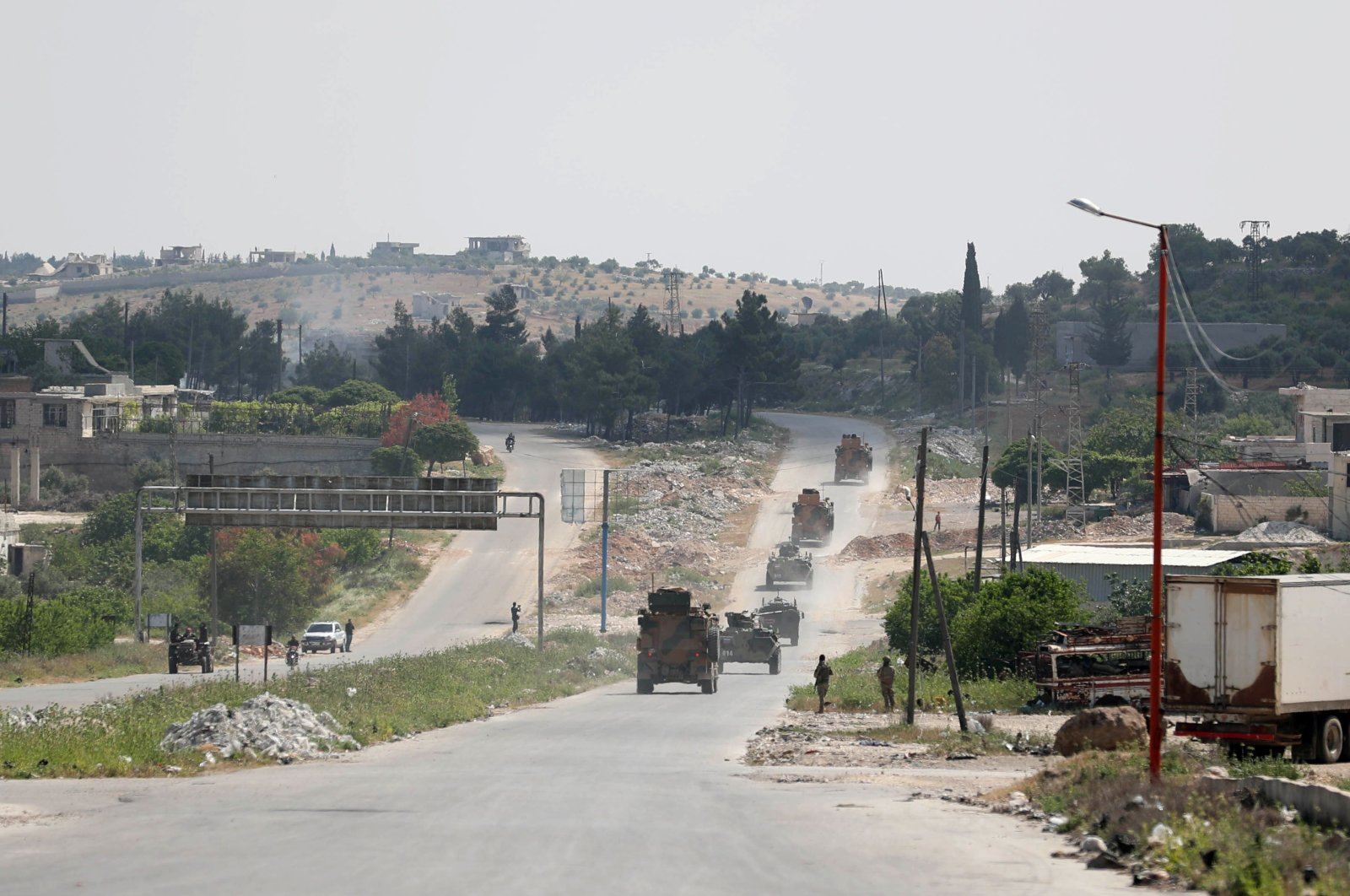 Military vehicles of a joint Turkish-Russian patrol pass through the M4 highway on the outskirts of the rebel-held town of Ariha in Syria's northwestern Idlib province on May 7, 2020. (AFP)
