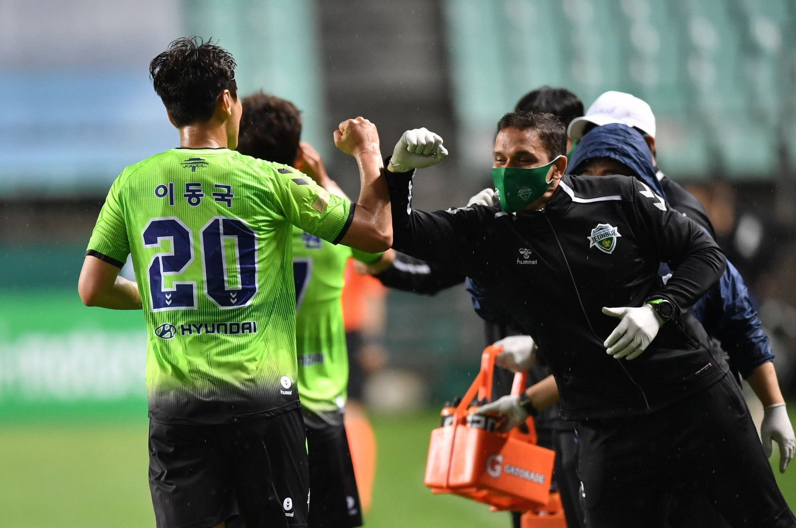 Jeonbuk Hyundai Motors' Lee Dong-gook (L) celebrates his goal with his mask-wearing team staff by bumping elbows to as a precaution against the pandemic, in Jeonju, South Korea, May 8, 2020. (AFP Photo)