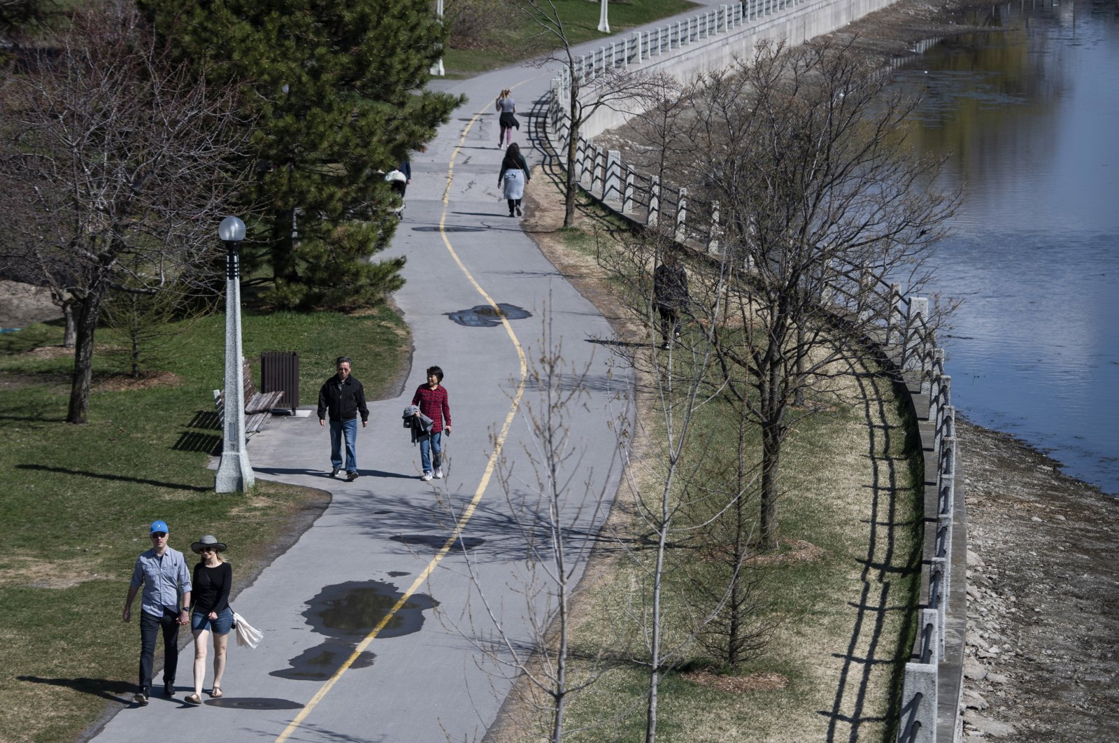 People walking along the Rideau Canal Western Pathway take advantage of warm weather in the midst of the COVID-19 pandemic, in Ottawa on May 3, 2020. (AP Photo)