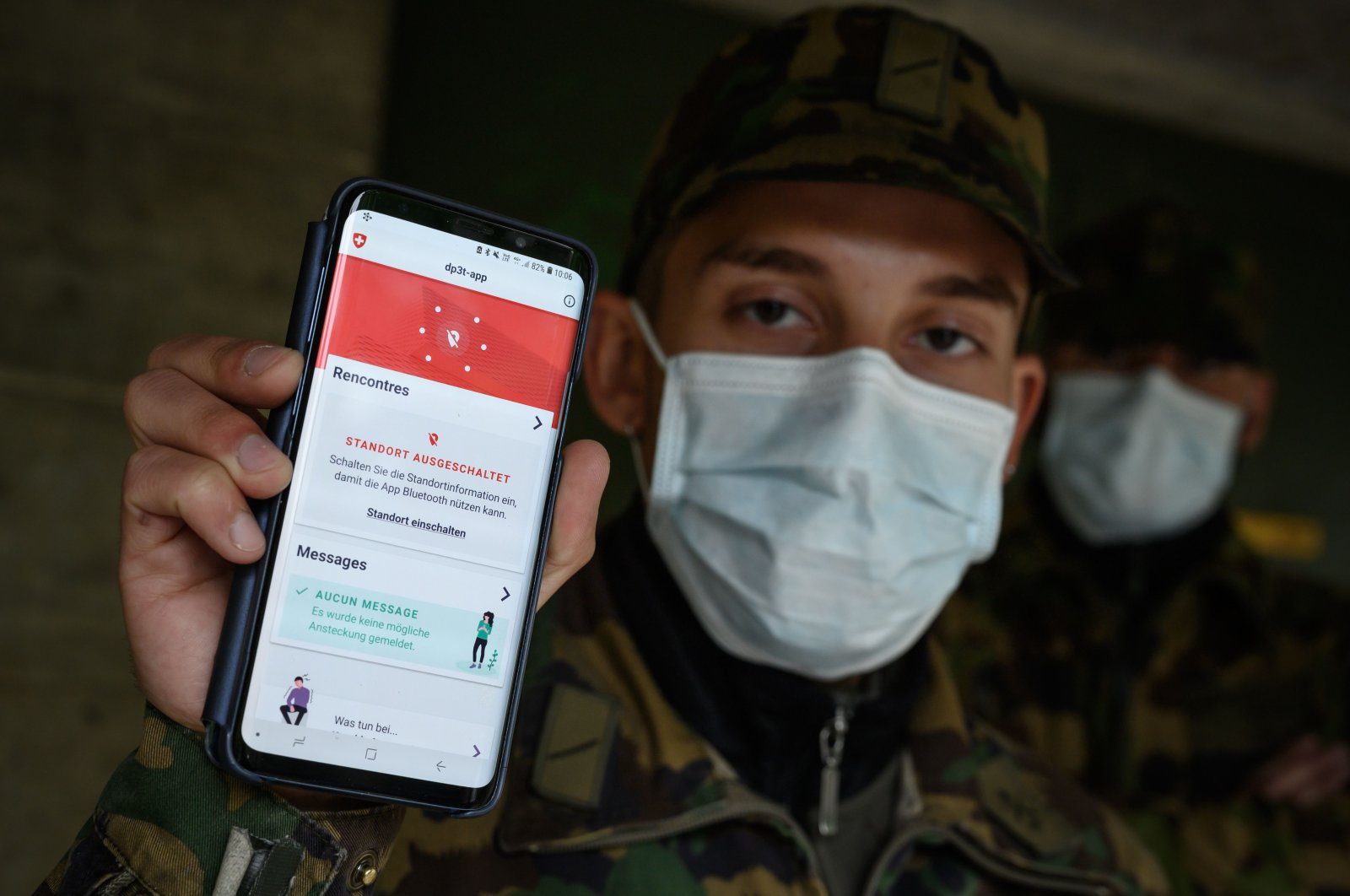 A Swiss soldier wearing a protective face mask poses with his smartphone at the Swiss army barracks of Chamblon on April 30, 2020.