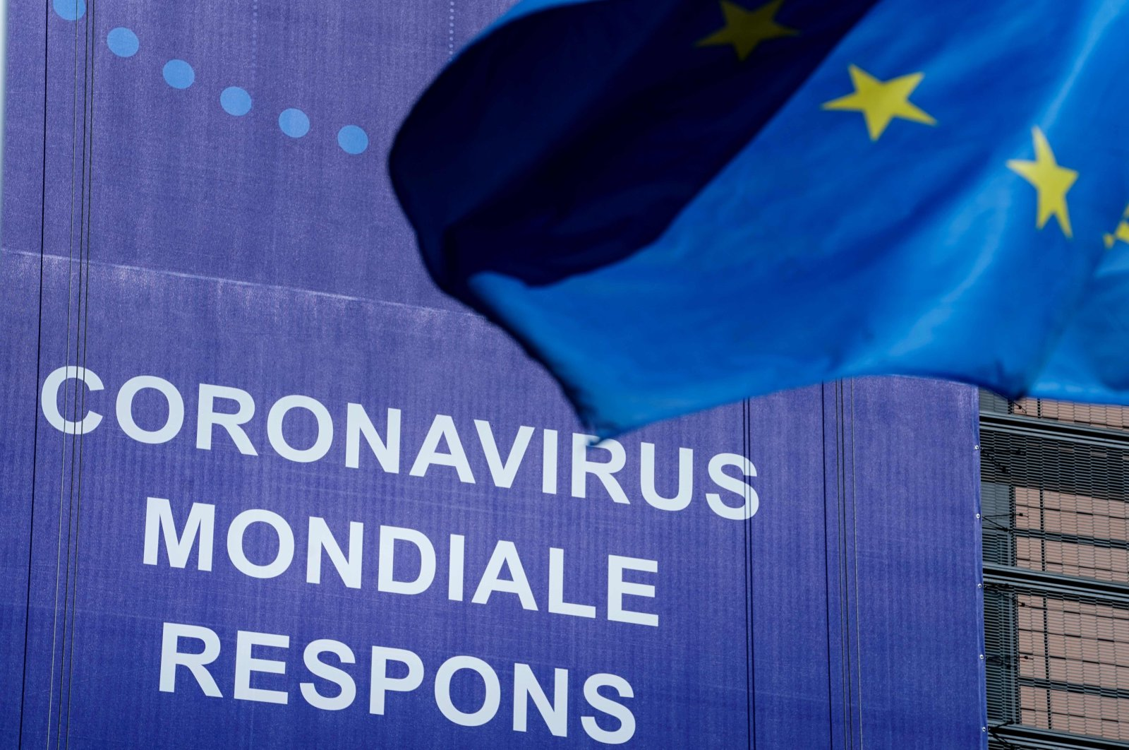 """An European Union (EU) flag flutters in front of a newly hung banner that reads """"Coronavirus Global Response"""" in front of The EU Commission building in Brussels, on May 6, 2020. (AFP Photo)"""