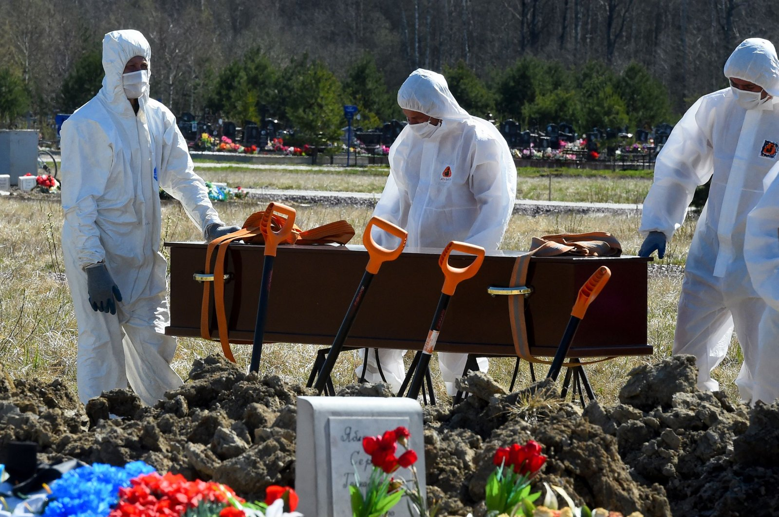 Cemetery workers wearing protective gear bury a coronavirus victim at a cemetery on the outskirts of Saint Petersburg, Russia, May 6, 2020. (AFP Photo)