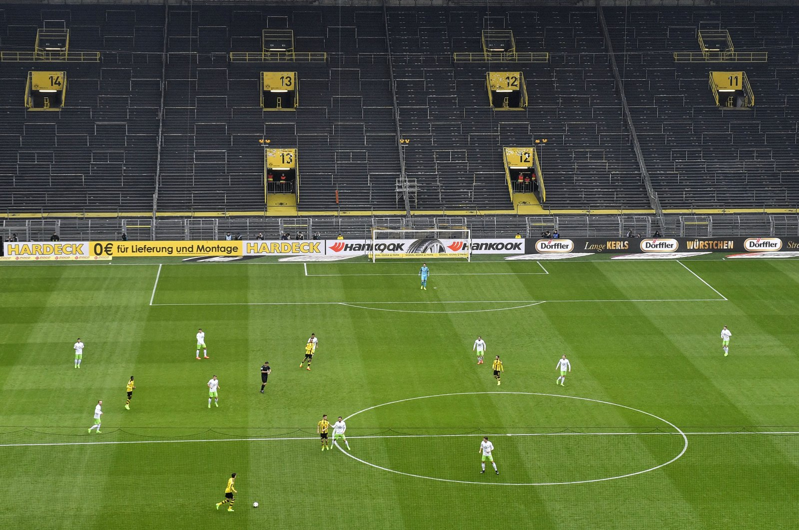In this Feb. 18, 2017 file photo, players challenge for the ball in front of the empty south tribune because of a ban following fan trouble during the German Bundesliga football match between Borussia Dortmund and VfL Wolfsburg at Germany's biggest stadium in Dortmund, Germany. (AP Photo)