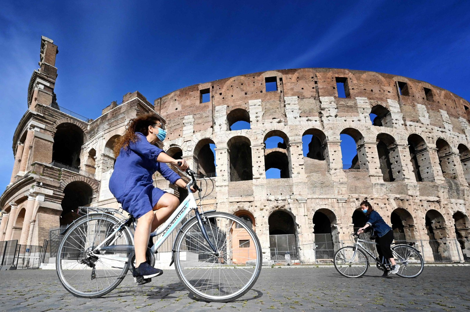 Women ride a bicycle past the Colosseum monument in Rome on May 8, 2020, during the country's lockdown aimed at curbing the spread of the COVID-19 infection, caused by the novel coronavirus. (AFP Photo)