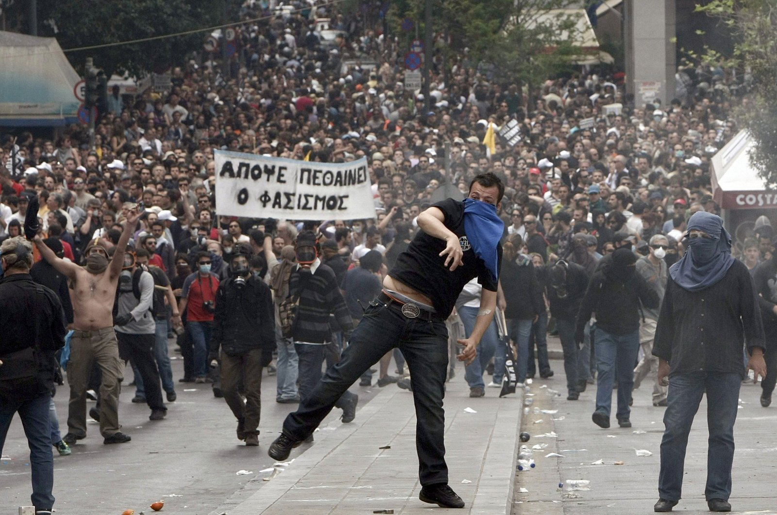 Demonstartors hurl projectiles at riot police near the Greek parliament in Athens during a nationwide strike in Greece, May 5, 2010. (Reuters Photo)
