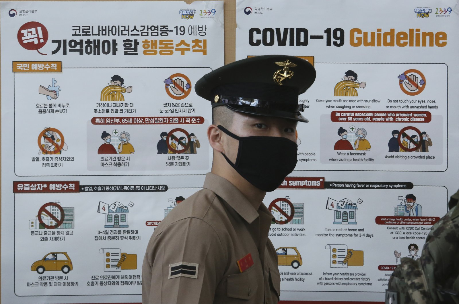 A South Korean Marine wearing a face mask stands in front of posters about precautions against the new coronavirus at Seoul Railway Station, South Korea, May 8, 2020. (AP Photo)
