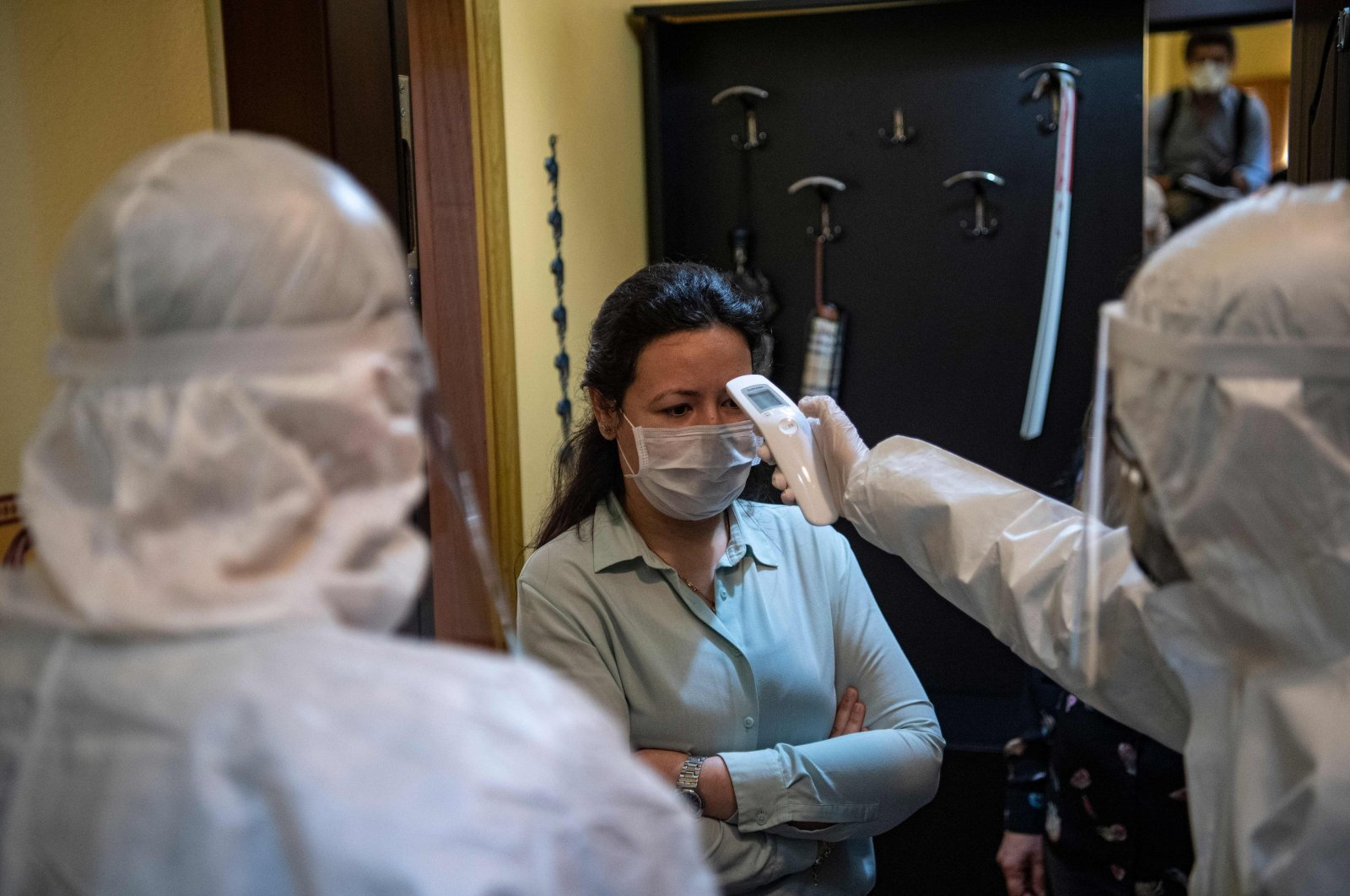 A health officer wearing protective clothing checks the temperature of a resident, believed to have been in contact with coronavirus patients, before collecting swab samples, in Istanbul on May 7, 2020. (AFP Photo)
