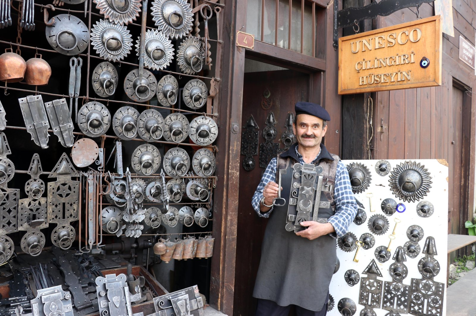 Master locksmith Hüseyin Şahin Özdemir poses with some of his works in front of his workshop on May 8, 2020 in Safranbolu. (AA Photo)
