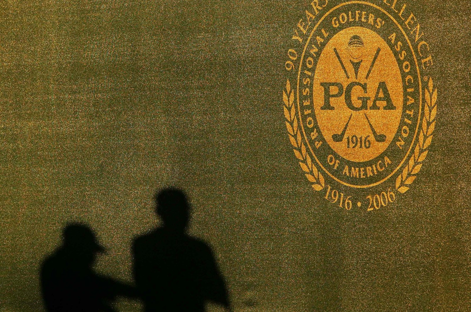 Two shadows of grounds crew are seen on the wall near the PGA logo during practice for the 2006 PGA Championship at Medinah Country Club in Medinah, U.S., Aug. 16, 2006. (AFP Photo)