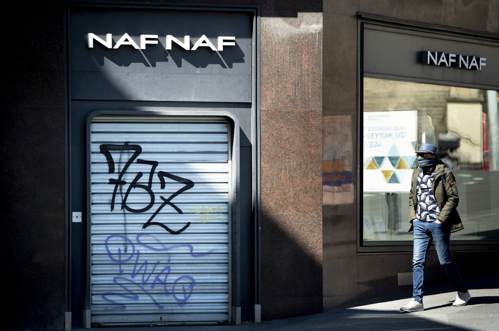 A man walks in front of a closed shop on a shopping street during the state of emergency for the COVID-19 outbreak, Lausanne, Switzerland, May 4, 2020. (AP Photo)