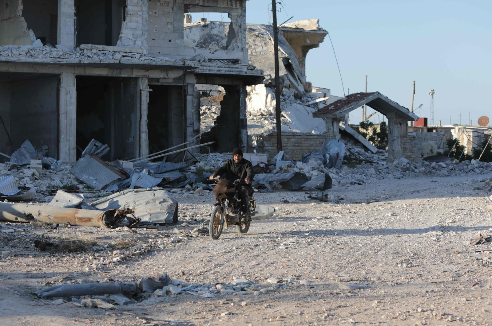 A Syrian man rides his motorcycle in al-Nayrab, a town ravaged by pro-regime forces' bombardment near the M4 strategic highway, Idlib, northwestern Syria, May 6, 2020.