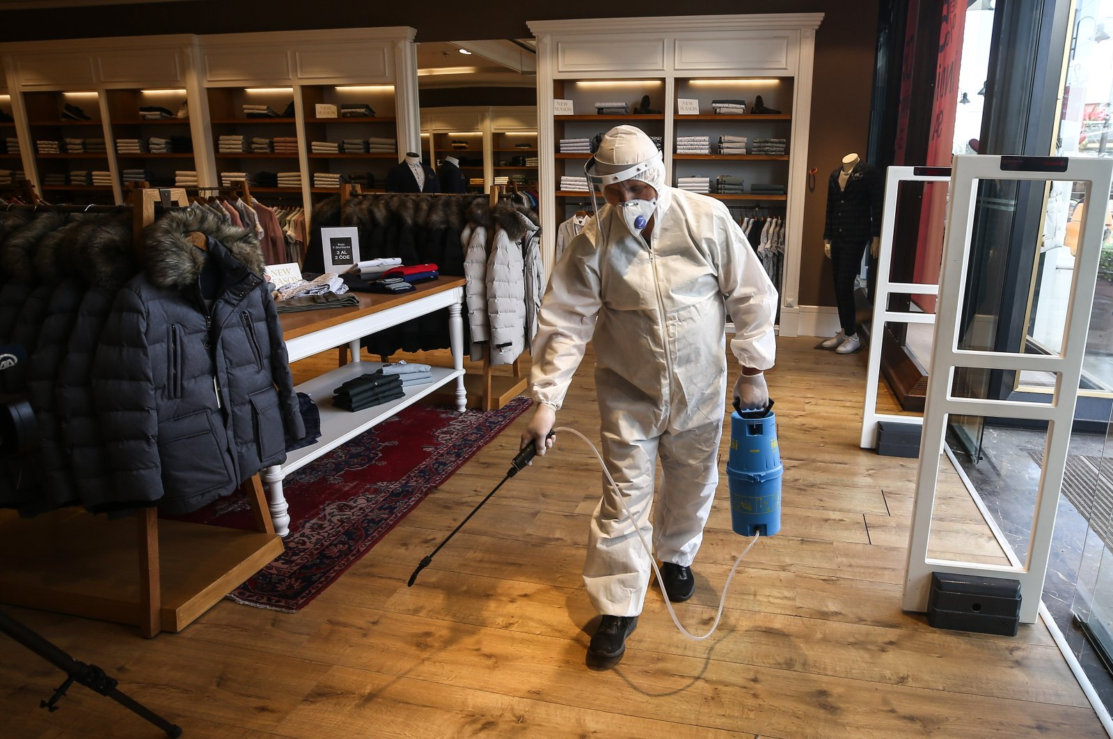 A worker sprays disinfectant at a store at a shopping mall in Istanbul, May 6, 2020. (AA Photo)