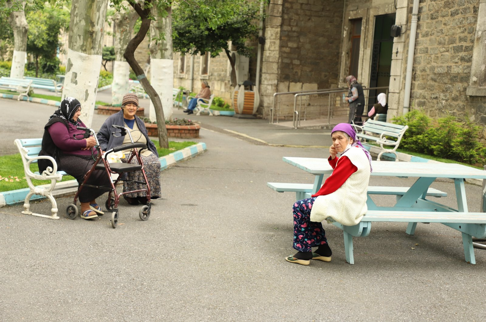 Residents of Darülaceze nursing home sit on benches in the courtyard, in Istanbul, May 10, 2020. (AA Photo)