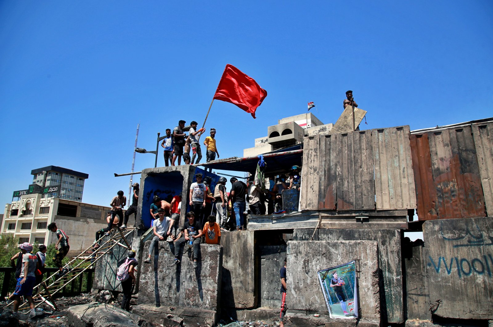 Anti-government protesters stage a sit-in on barriers set up by security forces to close the Jumhuriyah Bridge leading to the Green Zone government area, during ongoing protests in Baghdad, Iraq, May 10, 2020. (AP Photo)